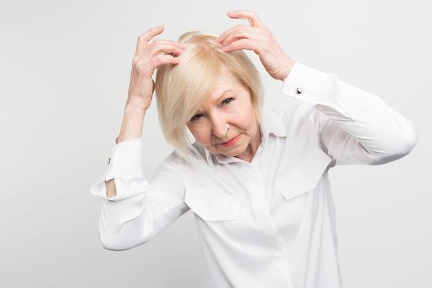 Deze vrouw heeft het probleem haar van haar hoofd te verliezen. ze heeft een behandeling nodig. anders zou ze zo snel mogelijk een pruik moeten gaan dragen. Premium Foto