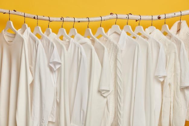 Dezelfde witte kleren op houten rekken in de kast. collectie kleding op hangers, geïsoleerd op gele achtergrond. Gratis Foto