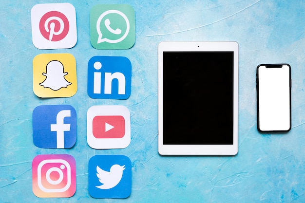 Dgital tablet en mobiele telefoon in de buurt van stickers van sociale media iconen Gratis Foto