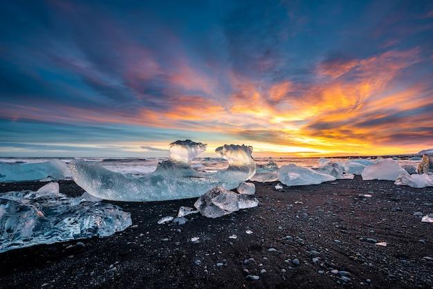 Diamant zwart zandstrand bij zonsondergang in ijsland Premium Foto