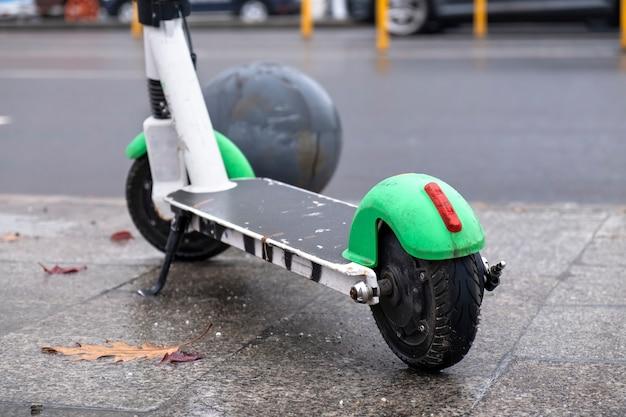 Dicht schot van een geparkeerde elektrische autoped dichtbij de weg met bewegende auto's, nat en bewolkt weer in boekarest, roemenië Gratis Foto