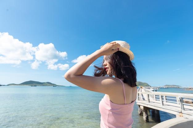 Dichtbij van aziatische vrouwentan huid die roze mouwloos onderhemd draagt en strohoed houdt. Premium Foto