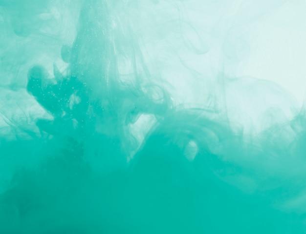 Dichte azuurblauwe wolk van waas in vloeistof Gratis Foto