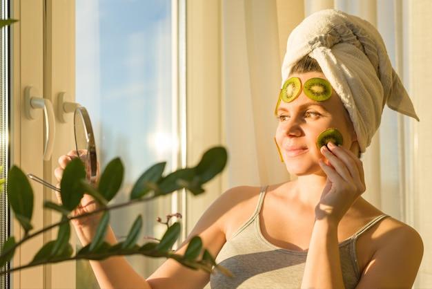 Dichte omhooggaand van de vrouw thuis dichtbij het venster met natuurlijk eigengemaakt fruit gezichtsmasker van kiwi op gezicht Premium Foto