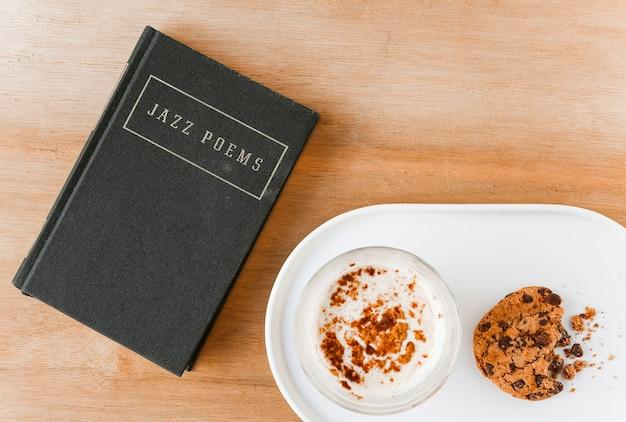 Dichtersboek met koffie en gegeten koekjes op plaat Gratis Foto