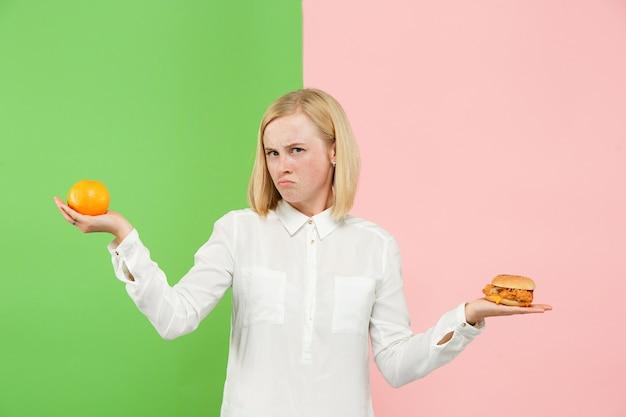 Dieet concept. gezond, nuttig voedsel. mooie jonge vrouw kiezen tussen fruit en ongezond fastfood in de studio. menselijke emoties en vergelijkingsconcepten Gratis Foto
