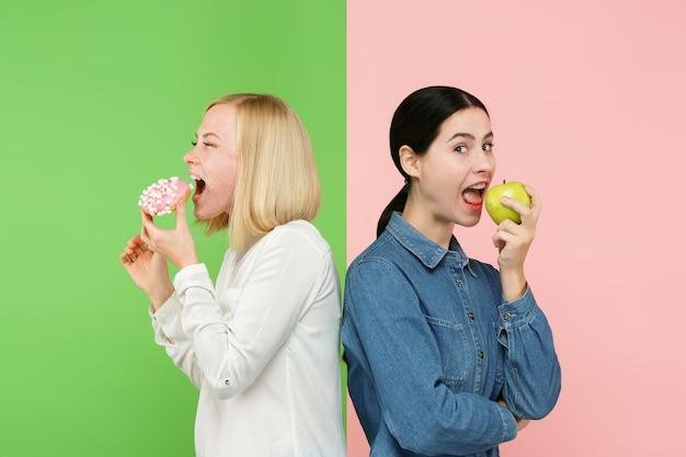 Dieet concept. gezond, nuttig voedsel. mooie jonge vrouwen die tussen fruit en ongezonde cake bij studio kiezen. Gratis Foto
