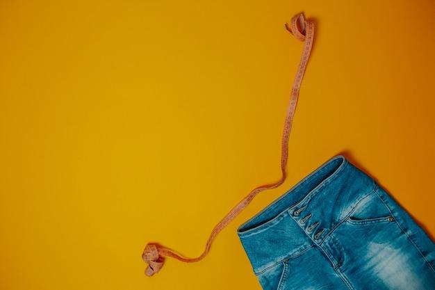 Dieet en gewichtsverlies thema. jeans en oranje meetlint met exemplaarruimte. Premium Foto