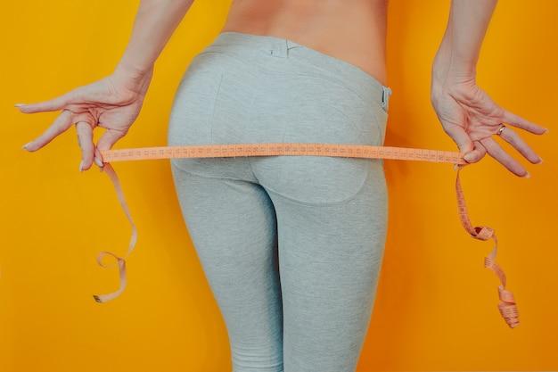 Dieet en gewichtsverlies thema. vrouw afgevallen. vrouw houdt meetlint en meet haar heupen. Premium Foto