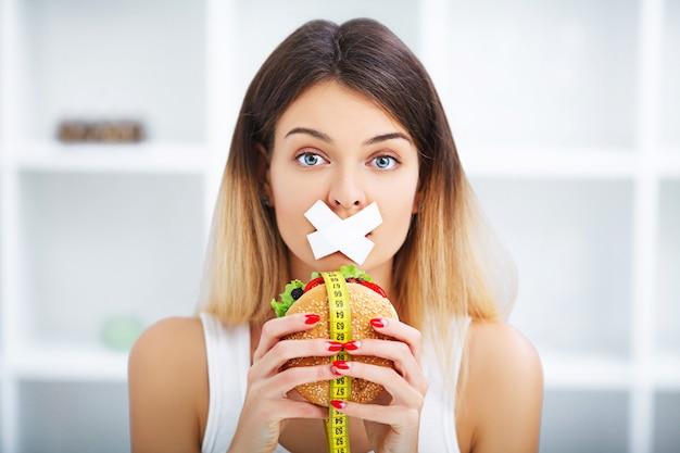 Dieet. jonge mooie vrouw die hamburger eet Premium Foto