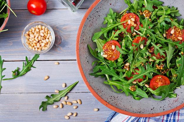 Dieet menu. veganistische keuken. gezonde salade met rucola, tomaten en pijnboompitten. plat leggen. bovenaanzicht Gratis Foto