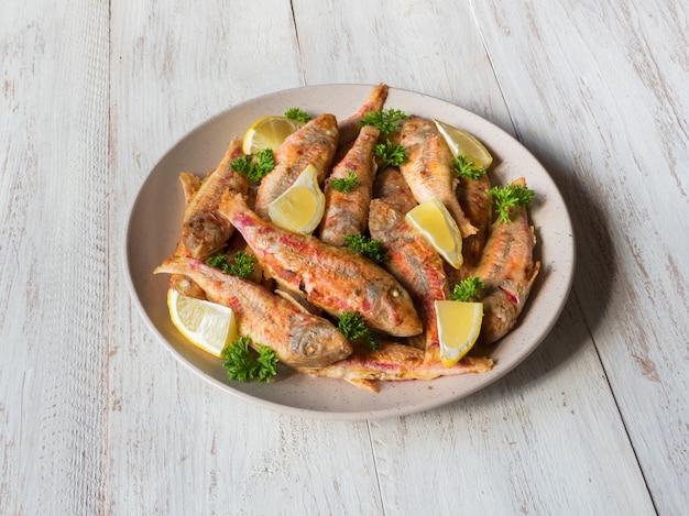 Dieet surmullet vis. gebakken vis in een plaat op een witte houten tafel. Premium Foto