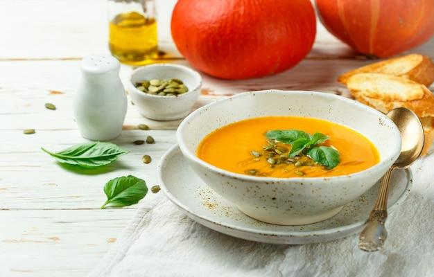 Dieet vegetarische pompoenroomsoeppuree met olijfolie, zaden en basilicum Premium Foto