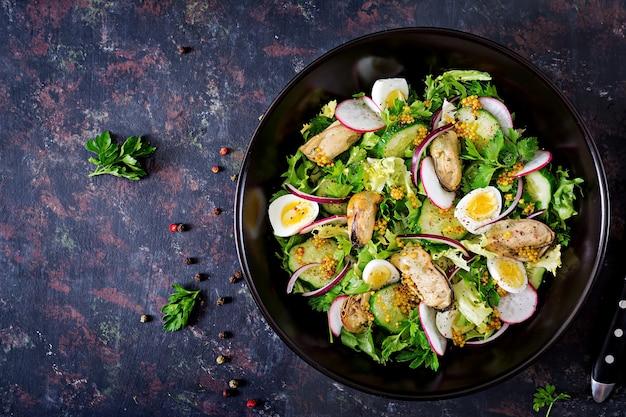 Dieetsalade met mosselen, kwarteleitjes, komkommers, radijs en sla. gezond eten. zeevruchten salade. bovenaanzicht plat leggen. Gratis Foto