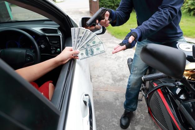 Dief met pistool op motorfiets steelt geld van vrouw in de auto Premium Foto