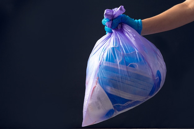 Dien medische handschoen in het gooien van vuilniszak Premium Foto