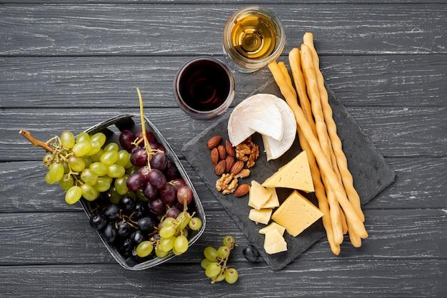 Dienblad met kaas en druiven naast glas met wijn Gratis Foto
