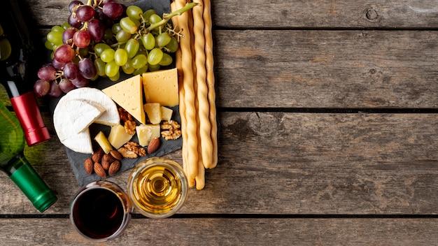Dienblad met kaas en druiven naast wijnfles Gratis Foto