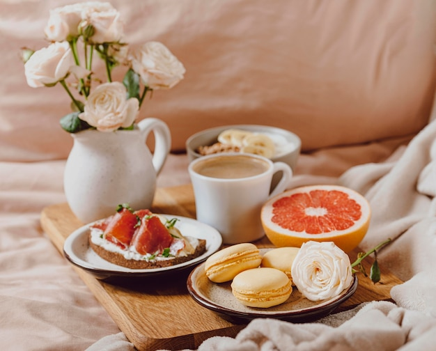 Dienblad met ochtendkoffie en sandwich in bed Gratis Foto