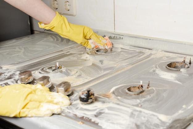 Dient gele handschoenen in die gasfornuis wassen. Premium Foto