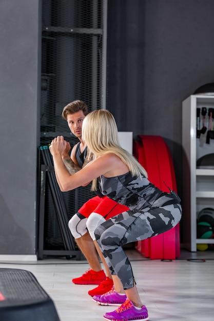 Diepe kraak. geschiktheidspaar in sportkleding die hurkende oefeningen doen bij gymnastiek. Premium Foto