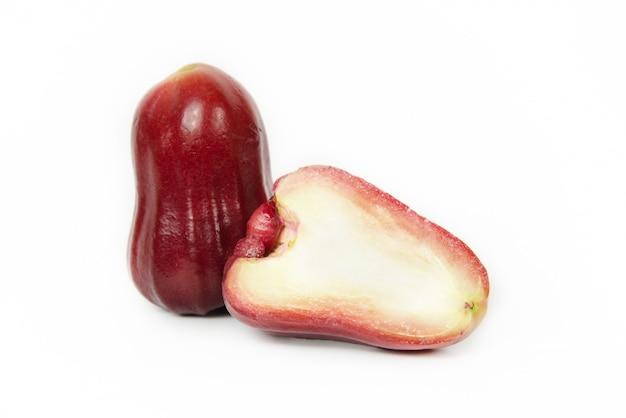 Diepte van het veld. groep djamboevrucht of java-appel of syzygiumzaad met volledig op houten dienblad. geïsoleerd op witte achtergrond. fruitsmaken van zoete rode glans. vers fruit. Premium Foto