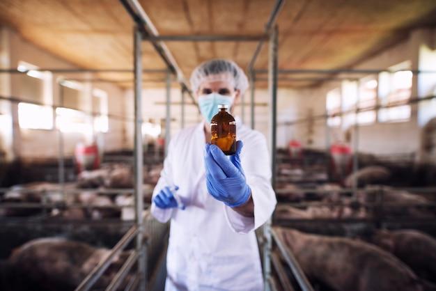 Dierenarts die in beschermende kleding fles met geneeskunde houdt bij varkensbedrijf Gratis Foto