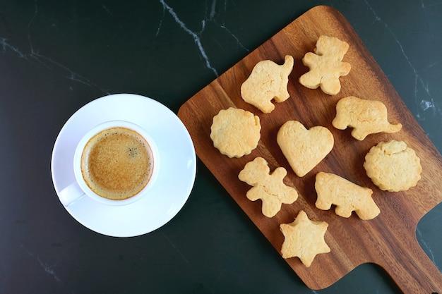 Dierlijke en hartvormige cookie met een kopje koffie op zwarte tafel Premium Foto
