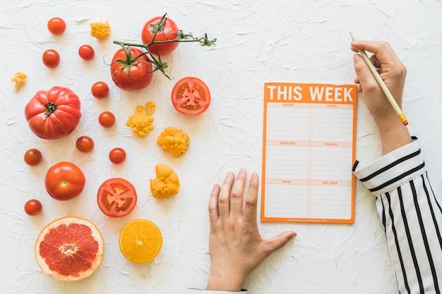 Diëtist die dieetweek met groente en vruchten op witte achtergrond plannen Gratis Foto