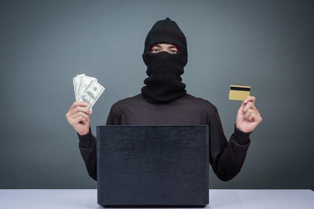 Dieven houden creditcards vast met behulp van een laptop voor het hacken van wachtwoorden. Gratis Foto