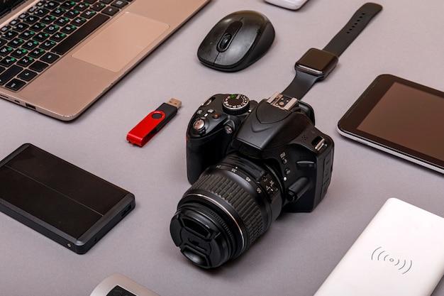Digitale camera, usb met externe harde schijf of batterij en uitrusting van de professionele fotograaf op grijs papier Premium Foto