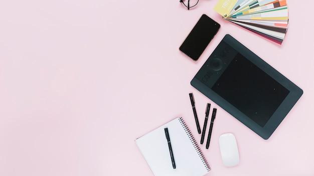 Digitale grafische tablet; mobiel en muis met spiraal notebook en viltstiften op roze achtergrond Gratis Foto
