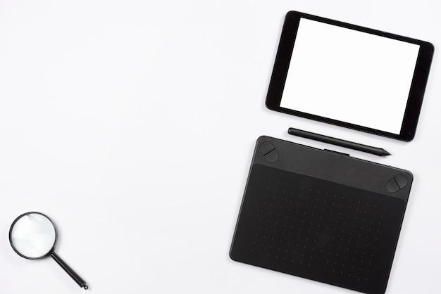 Digitale tablet en grafische digitale tablet met stylus en vergrootglas op witte achtergrond Gratis Foto