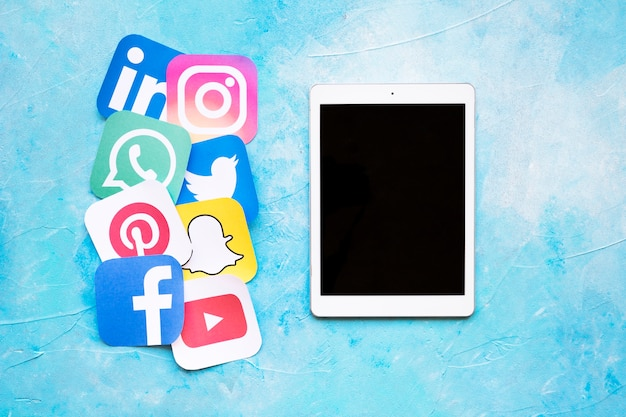 Digitale tablet geplaatst in de buurt van afgeronde iconen van sociale media afgedrukt op papier uitgesneden Gratis Foto