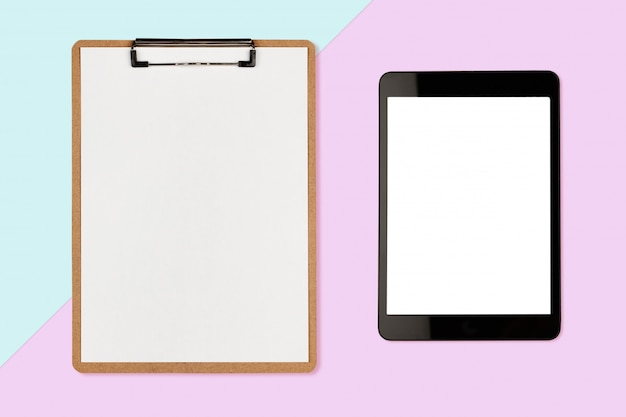Digitale tablet met leeg scherm en klembord op pastel kleur achtergrond Premium Foto