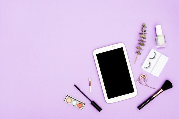 Digitale tablet met oogschaduwpalet; make-up kwast; nagellakfles; mascara borstel en nagellak fles op paarse achtergrond Gratis Foto