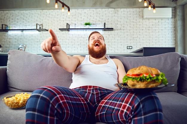 Dikke grappige man in pyjama met een hamburger zittend op de bank. Premium Foto