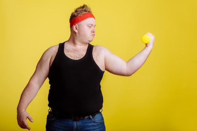 Dikke man met halter op gele muur. motivatie voor dikke mensen Premium Foto