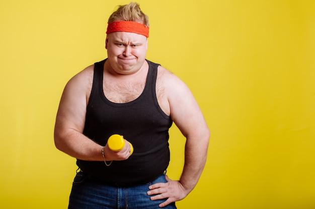 Dikke man probeert kleine gele dumbell op te tillen Premium Foto