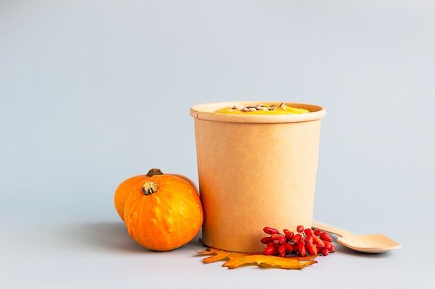 Dikke vegan pompoenroomsoep met zaden in een wegwerpbeker. soep voor onderweg, bezorging van gezond eten. Premium Foto