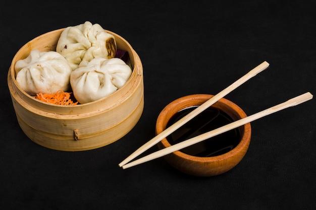 Dim sum samen met wortelsalade die in kleine stoombootmand wordt gediend en de kom van de sojasaus met eetstokjes op zwarte achtergrond Gratis Foto