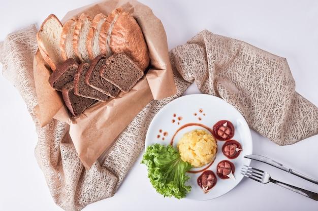 Diner menu met gebakken worstjes, aardappelpuree en bonen geserveerd met sneetjes brood. Gratis Foto