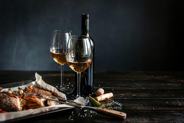 Dinerconcept met twee glazen witte wijn, gebakken vissen Premium Foto