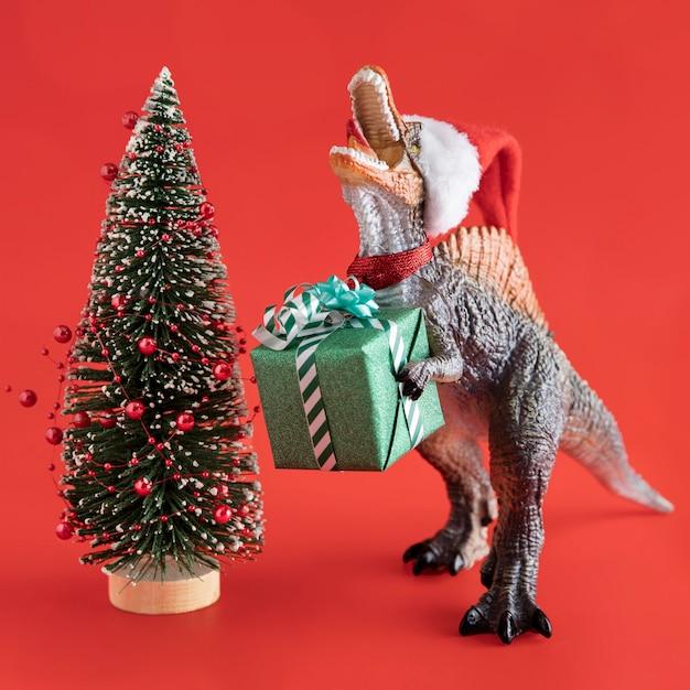 Dinosaurus speelgoed met cadeau en boom Premium Foto