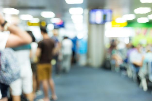 Disfocus van mensen die samen op de luchthaven wachten voor het vertrek van het vliegtuig met bagage Premium Foto