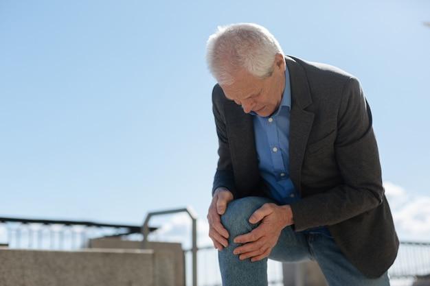 Dismal gefrustreerde oude man die zichzelf op zijn knie oprichtte terwijl hij zijn handen vasthield terwijl hij vreselijke pijn voelde Premium Foto