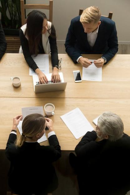 Diverse bedrijfscollega's die op vergadering, verticale hoogste mening samenwerken Gratis Foto