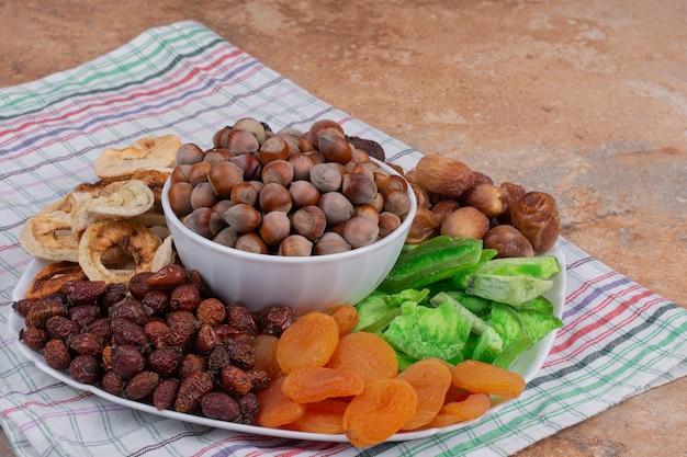 Diverse gedroogde vruchten en noten op een witte plaat. Gratis Foto