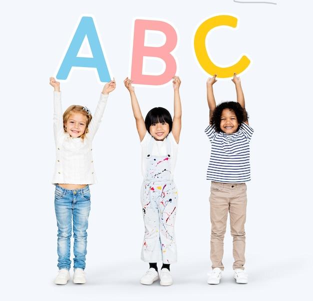 Diverse gelukkige kinderen die het abc leren Premium Foto