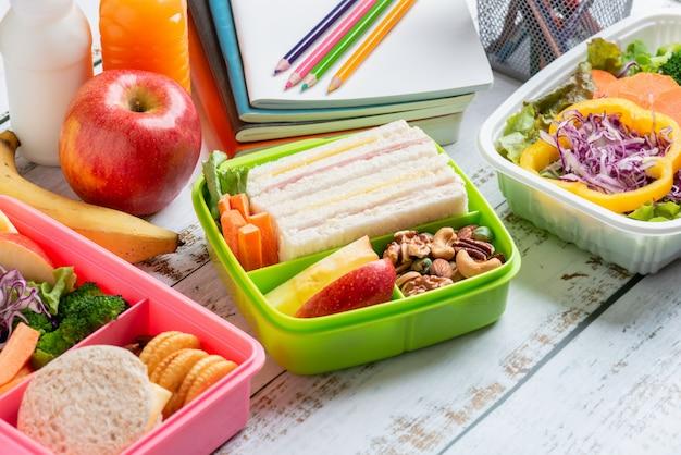 Diverse gezonde lunchdozen sandwich. kid bento pack voor schoolset in plastic verpakking, sladoos, banaan en appel met sinaasappelsap, melk. Premium Foto